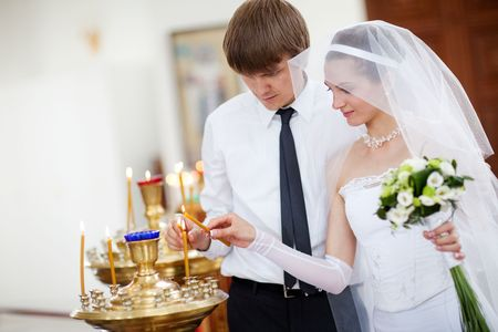 couple lighting candles in a church Stock Photo - 6305833