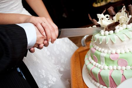 hands of bride and groom cut of a slice of a wedding cake   photo