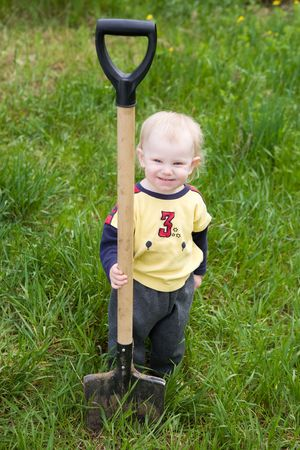 small girl with the shovel in the garden