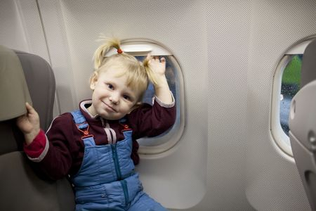 child in the airplane near the window photo
