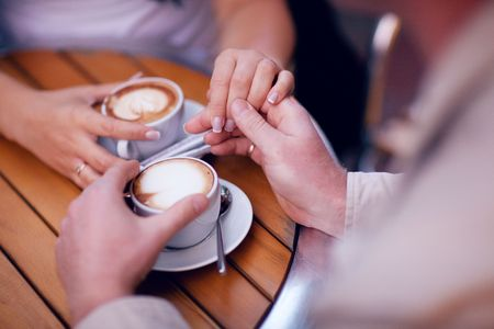 two hands and cup of coffee