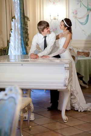 happy bride and groom at the piano photo