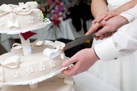 rebanada de pastel: manos de novios cortan de un segmento de un pastel de boda  Foto de archivo