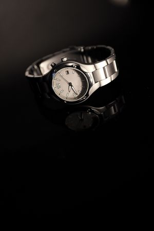 wristwatch on the glass on black background photo