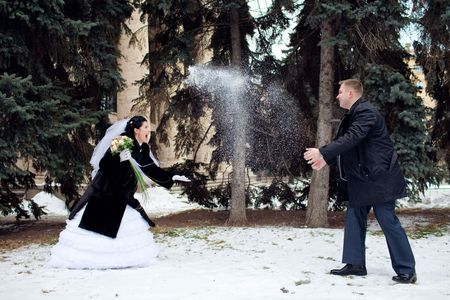 winter wedding: bride and groom playing snowballs Stock Photo