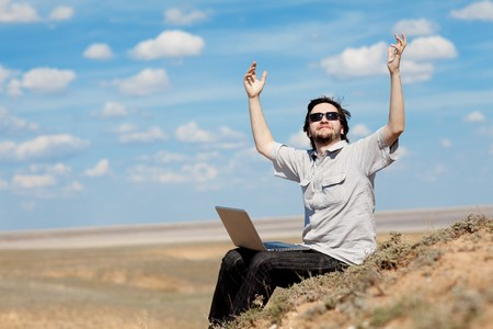 man with laptop on the mountain photo