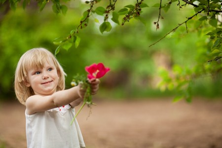 happy small girl with tulip outdoors in sunny day photo