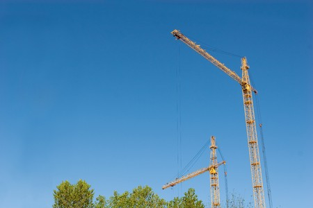 two hoisting cranes and the sky photo