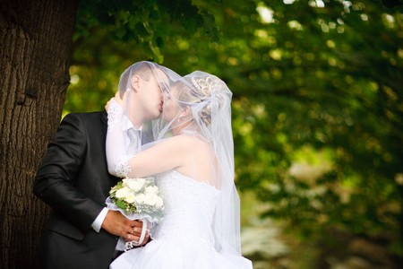 kiss of bride and groom outdoors photo