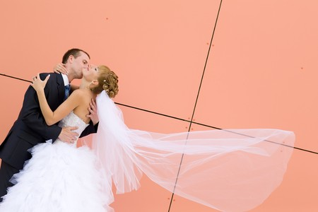 kiss of bride and groom near the wall