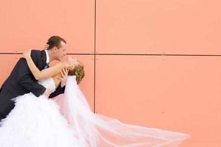 Kuss der Braut und Bräutigam in der Nähe der Wand  Standard-Bild