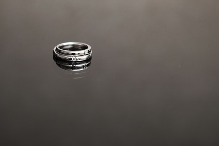 wedding rings on the glass table in black and white photo