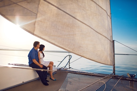 catamaran: man and girl under the sail
