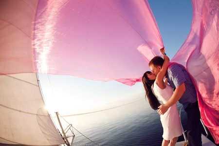 man and girl  kissing under the sail
