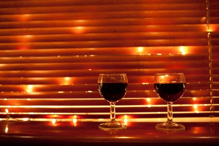 two red wine glasses in lights photo