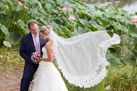 bride and groom near the lotus pond Stock Photo - 9070415