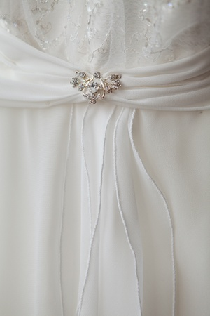 part of a wedding dress with brooch photo