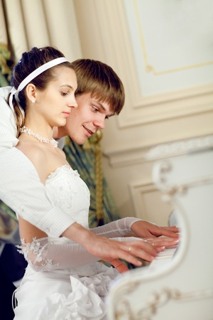 man teaching his bride to play the piano photo