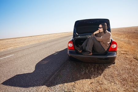 man in trunk of car eating apple photo