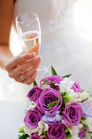 glass of champagne in a hand of a bride photo