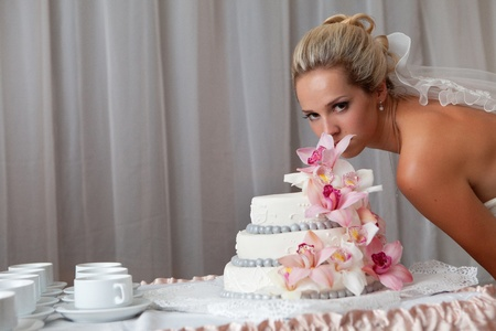 bride near a wedding cake with pink flowers