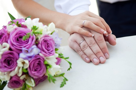 girl with rings: hands of bride and groom with bouquet