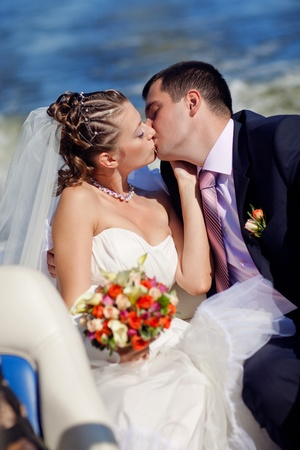 bride and groom kissing on the boat photo