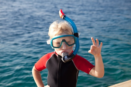 child in a diving mask showing ok