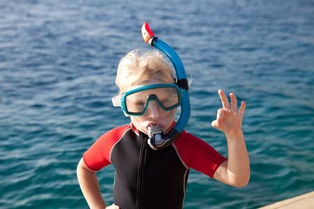 Kind in einer Tauchermaske zeigt ok