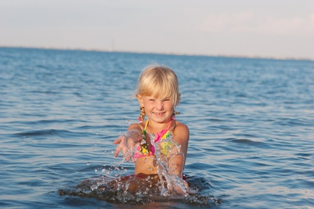 happy girl splashing in water at the evening photo