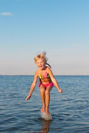 happy girl jumping in water at the evening photo