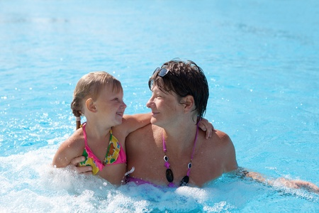 little girl with her grandmother in the swimming pool photo