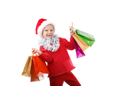 child in Santas cap with presents in bags photo