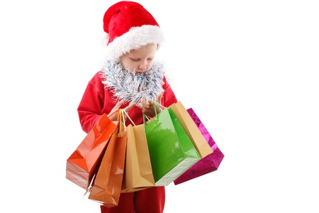 child in Santas cap with presents in bags counting fingers photo