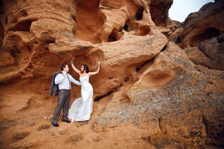 rock climb: bride and groom on the mountain Stock Photo
