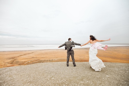 bride and groom on the mountain ready to jump photo