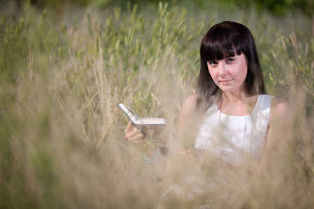 girl reading a book in the grass Stock Photo - 12470921