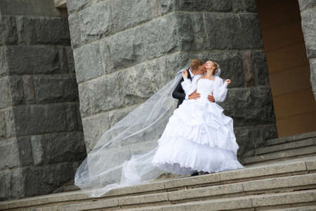 bride and groom kissing near the wall photo