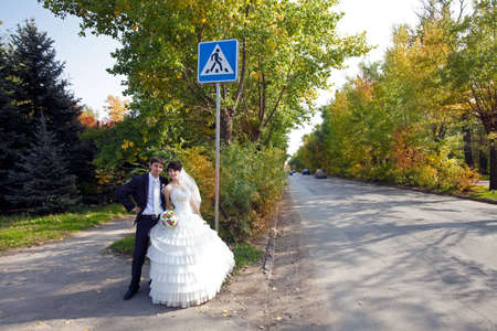 bride and groom near the sign on the road photo