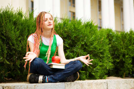 girl with a book meditating near the school photo