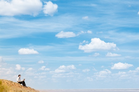 man with laptop and blue sky