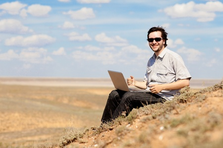 man with laptop outdoors photo