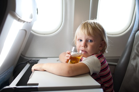 child with juice in airplane photo