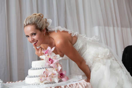 bride near a wedding cake with pink flowers photo