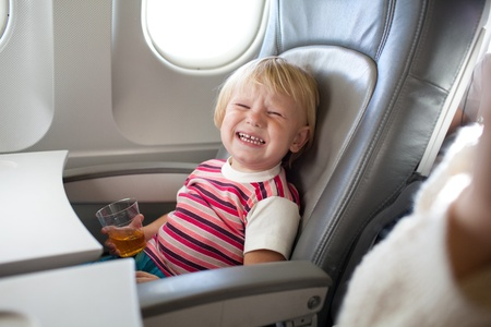crying child with juice in airplane Standard-Bild