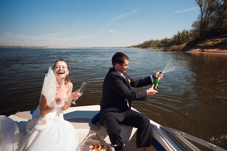 bride and groom with champagne on the boat photo
