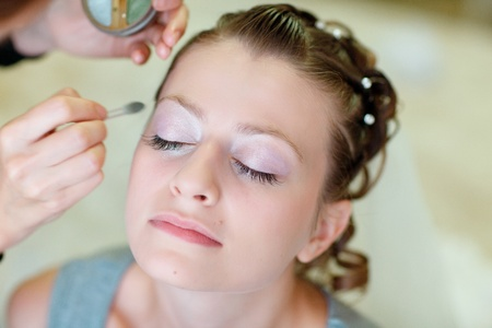 girl applying wedding make-up by professional make-up artist photo