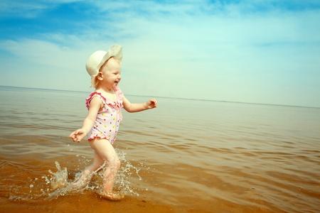 seashores: happy small girl running on the beach