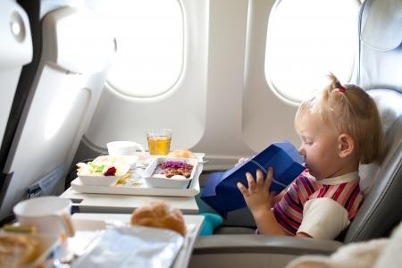 niña pequeña con bolsillo en el avión Foto de archivo