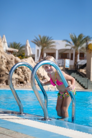 pretty little girl on the ladder of the pool photo